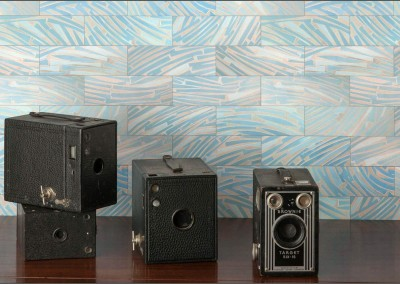 "Art Deco Blue Glass (DE4249)-Subway : Wallpaper Pattern created from Blue Glass, Repeat 18w x 24.29h. Shown with, from left bottom, Unknown Kodak Brownie, Kodak ""No. 2-A Brownie"", Kodak ""No. 3 Brownie"" and Kodak ""Brownie Target Six-16"".  © Doug Garrabrants 2014"