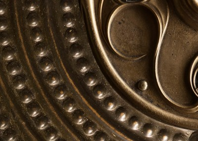 Shielded (DE9707)-Detail : Hammered brass shield of rings and dots with ornate center. 45 inch repeat. © 2014 Doug Garrabrants
