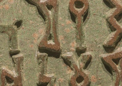 Verdigris Runes (DE9697)-Detail ; Panels of runes in a verdigris bronze field. Wallpattern with a 25 inch repeat. © 2014 Doug Garrabrants