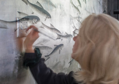 Lena painting a switch plate to blend with de Gournay wallpaper.